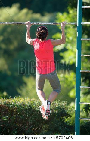 Strong woman athlete is Chin-ups and Pullups training on an abandoned sports field. Pull-up on the bar. Athlete Outdoors.