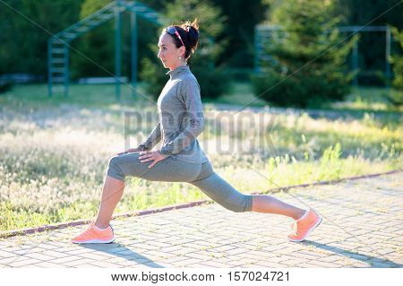 Athletic young woman working out in the countryside. Training her muscles to increase her suppleness