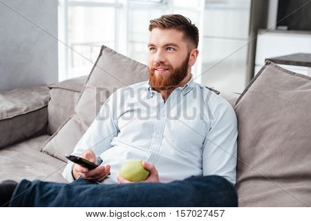 Man on sofa watching TV. with apple
