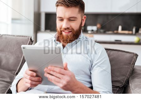 Young man with tablet on sofa. slose up portrait
