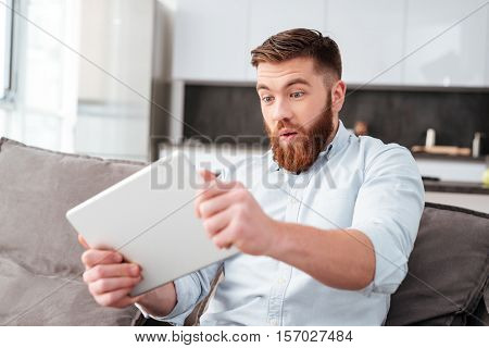 Bearded man with tablet on sofa. so funny man