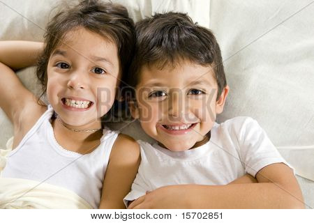 Cute brother and sister laying in bed