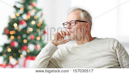 old age, holidays, problem and people concept - senior man in glasses thinking at home over christmas tree background