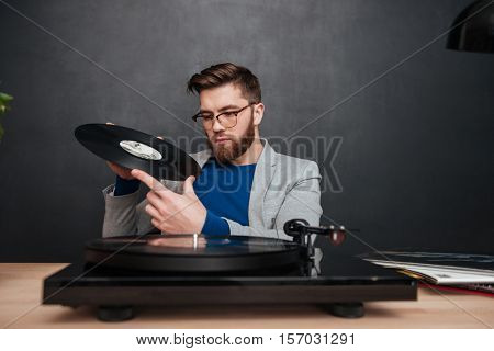 Pensive bearded young man in glasses with turntable and vinyl record sitting and thinking