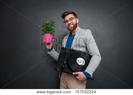 Cheerful bearded young businessman in glasses with flowers in pot and turntable