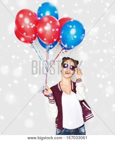 winter, christmas, people, holidays, party and summer concept - happy smiling pretty teenage girl in sunglasses with helium balloons over gray background and snow