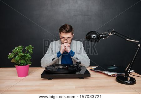 Thoughtful young businessman with turntable sitting at the table and thinking