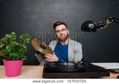 Handsome bearded young businessman in glasses with turntable and golden vinyl record
