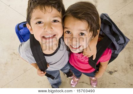 Pequeño niño y niña con sus mochilas