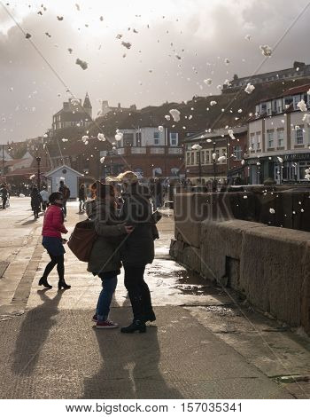 WHITBY ENGLAND - NOVEMBER 5: Tourists avoid sea foam whipped up by high wind. In Whitby North Yorkshire England. On 5th November 2016.