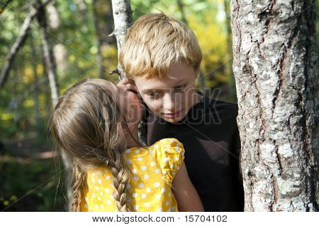 Little girl whispering to a little boy