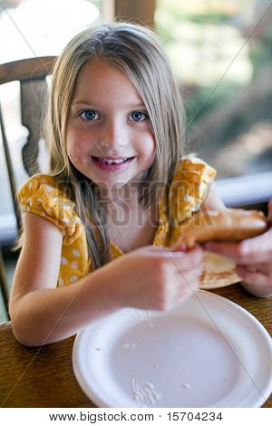 Little girl eating at the table