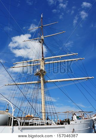 the mast of the ship sailing ship on a background of blue with clouds sky