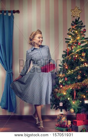portrait of nice young woman hanging around christmas tree on x-mas  eve