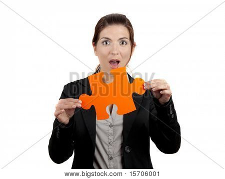 Business woman with a astonish expression, holding a big piece of puzzle, isolated on white