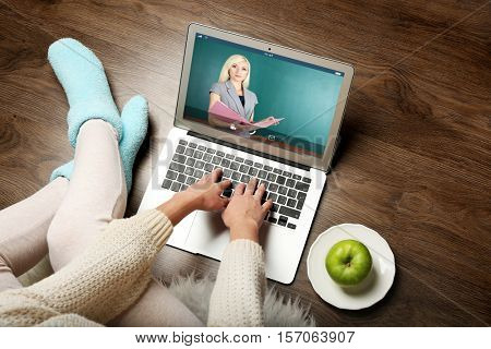 Woman video conferencing with tutor on laptop at home. Distance education concept.