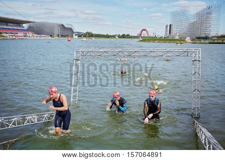 MOSCOW, RUSSIA - AUG 14, 2016: Participants of swimming stage of traditional 3Grom series triathlon contest in Krylatskoye Rowing Channel.