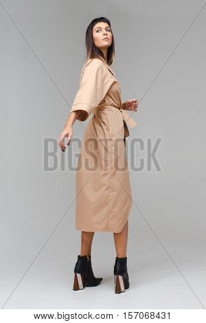 Model looks up relegating hand side at photo studio posing in white cloak