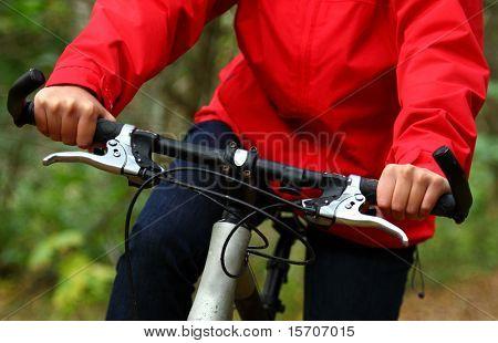 Biking in the forest.. Closeup of woman on mountainbike.