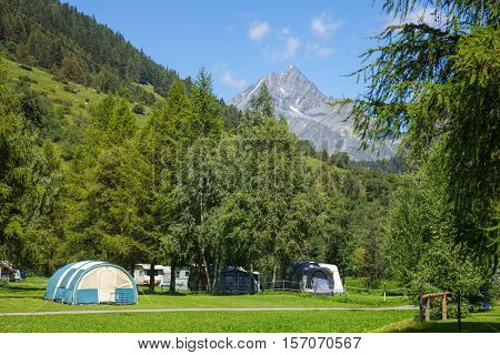 Tents at a campsite in Switzerland on a sunny summer day with Alps in background