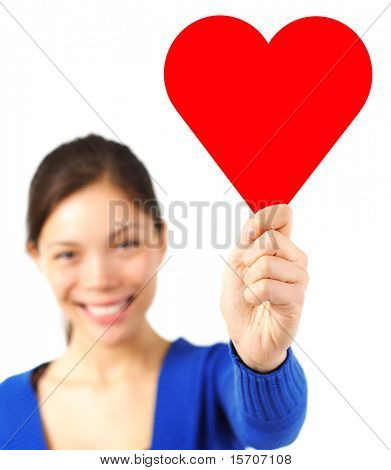 Cute woman in love holding a heart shape copy space to put your text in. Isolated on white background, focus on the heart sign.