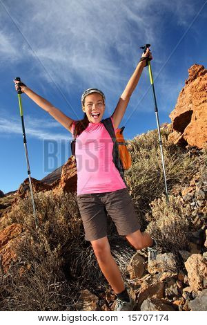 Happy woman hiker holding her arms in the air in a feeling of success having reached the summit. From a hike / backpacking trip in the beautiful landscape in the park on the volcano, Teide, Tenerife