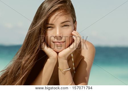 Beautiful portrait of young brunette mixed race Asian Caucasian woman on beach with sepia filter for a vintage look. Serene looking model with healthy brown hair relaxing on beach on vacation travel.