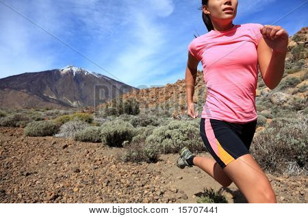 Running. Woman Cross country trail runner running on the mountain / volcano Teide on Tenerife. Beautiful mixed chinese asian / caucasian female model.