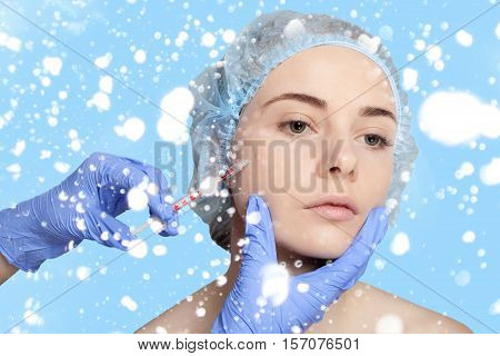 Attractive young woman gets cosmetic injection an injection in the upper lip over blue background. Doctors hands making an injection in face close-up. Beauty Treatment. over snow background