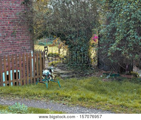 an old rustic metal rocking horse is in a green garden. Brick wall and timber fence behind
