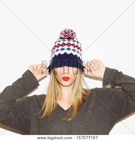 Portrait of cute, cheerful, modern young blonde Caucasian woman in knitted beanie hat and gray oversize blouse, isolated on white. Studio lighting, retouched.