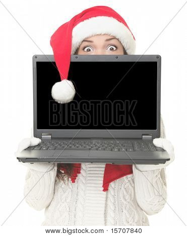 Christmas internet shopping. Woman in santa hat shocked holding computer with blank screen for advertising message