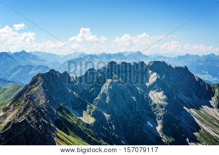 High altitude view on German alps with sharp peaks and partly cloudy sky with copy space above