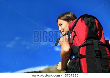 Hiker looking while backpacking / hiking in nature. Copy space on blue sky.