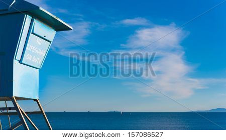A closed lifeguard stand or hut on ocean coast.  Danger sign