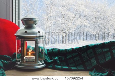 Winter background-lantern with burning candle on windowsill and winter forest outdoor.Winter still life with winter concept -winter background. Winter background evening with cohome and winter outside