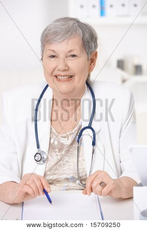 Senior female doctor, wearing white coat and stethoscope, working at desk, smiling.?