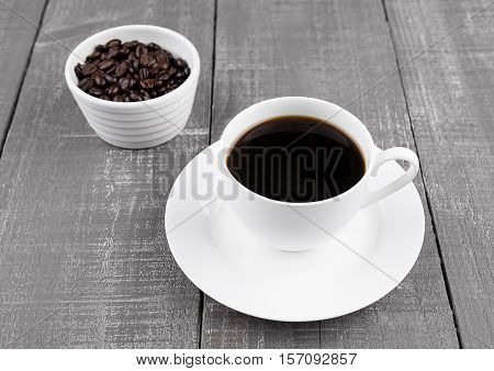 Cup of black coffee for breakfast with beans on wooden background