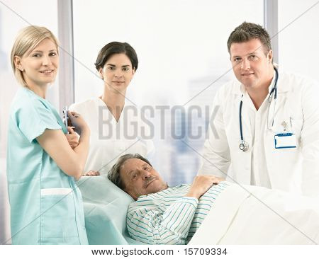 Portrait of senior patient lying in bed, surrounded with hospital crew, smiling at camera.?