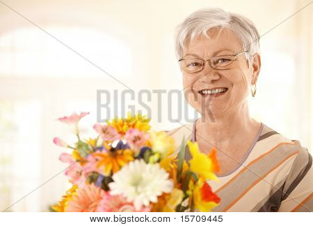 Closeup portrait of happy senior woman holding flowers looking at camera, smiling.?