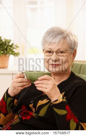 Older lady sitting at home with tea cup, smiling at camera.?