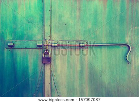 old closed metal door with lock close-up in retro style