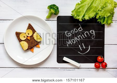 children's breakfast owl shaped sandwich on white plate with vegetables and fruits top view at wooden background good morning