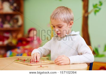 Cute Boy, Kid With Special Needs Solving A Puzzle In Rehabilitation Center