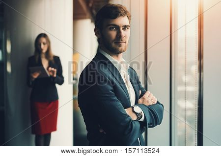 Group of business people in office interior: serious man in formal suit in front and woman in red dress and jacket behind man standing near window