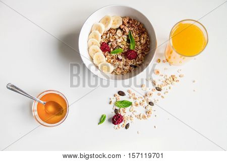 Breakfast with oatmeal and orange juice on white background top view