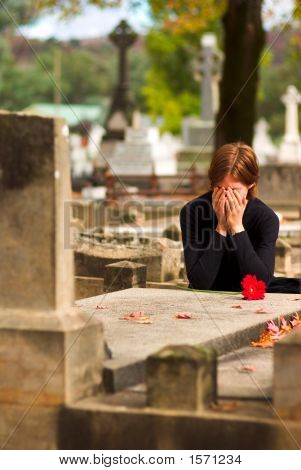 Woman Laying Flower On Grave
