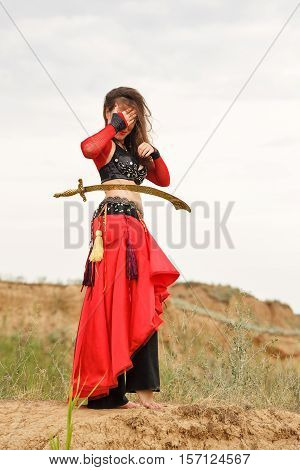 Oriental Beauty dance with a sword. Tribal style. Lovely girl in costume dancing outdoors. Nomads. A sword is on the thigh of the girl.