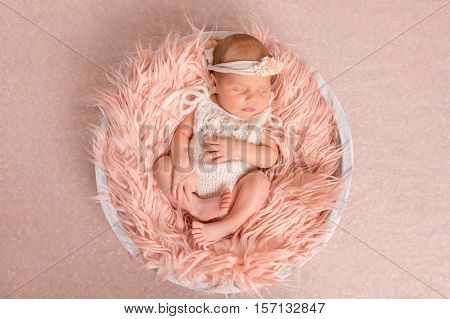 sweet newborn girl in white romper sleeping on round cot with fluffy blanket, top view