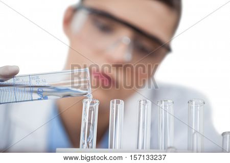 Female scientist conducting an experiment against white background